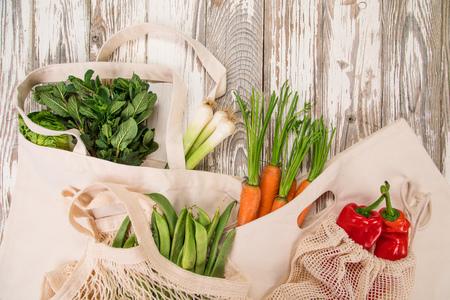 Verse groenten in bio eco katoenen tassen op oude houten tafel. Winkelconcept zonder afval.