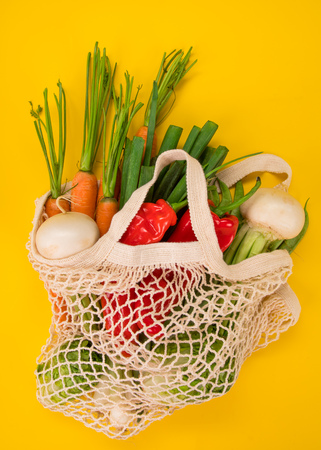 Fresh vegetables in bio eco cotton bags on yellow background. Zero waste shopping concept. Фото со стока