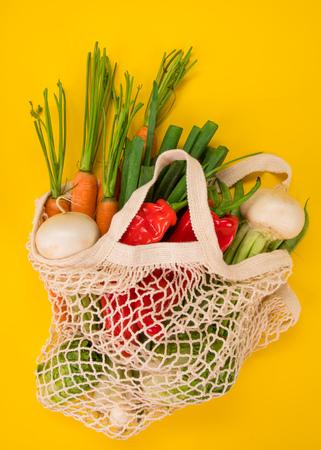 Légumes frais dans des sacs en coton bio éco sur fond jaune. Concept d'achat zéro déchet.