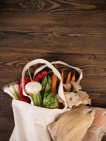 Fresh vegetables in bio eco cotton bags on old wooden table. Zero waste shopping concept. Stock Photo