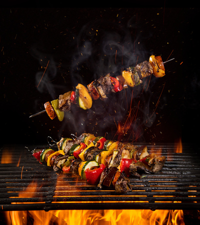 Tasty skewers on the grill with flames