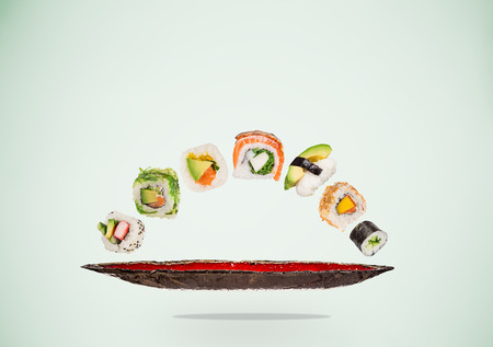 Pieces of delicious japanese sushi frozen in the air. Standard-Bild - 119167104