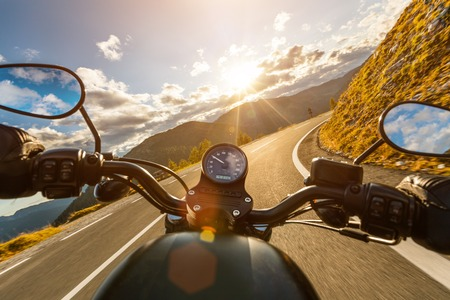 Motorcycle driver riding in Alpine highway, handlebars view, Austria, Europe. Zdjęcie Seryjne