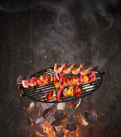 Kettle grill with hot briquettes, cast iron grate and tasty skewers flying in the air. Stok Fotoğraf - 123560929