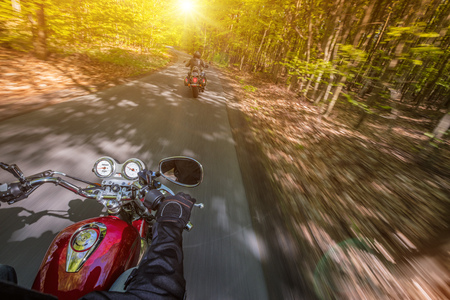 Motorcycle driver riding in spring forest. Stok Fotoğraf