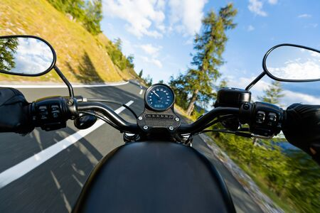 Motorcycle driver riding in Alpine highway, handlebars view, Austria, Europe. 免版税图像