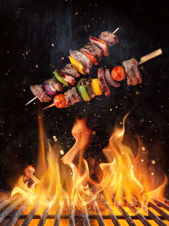 Tasty skewers flying above cast iron grate with fire flames.