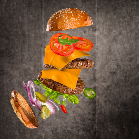 Tasty cheeseburger with flying ingredients on dark background Stock Photo