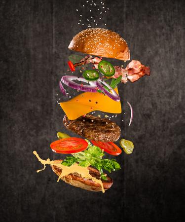 Tasty cheeseburger with flying ingredients on dark background 写真素材