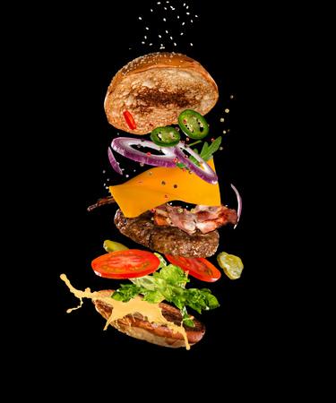 Tasty hamburger with flying ingredients on dark background