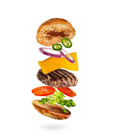 Tasty hamburger with flying ingredients on white background
