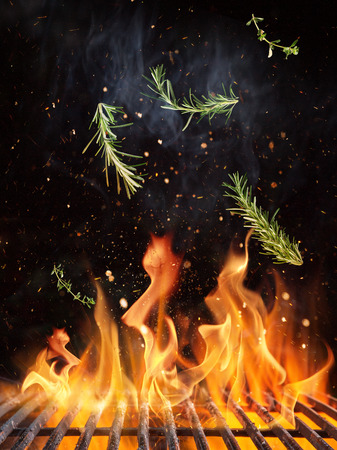 Rosemary flying above cast iron grate with fire flames.