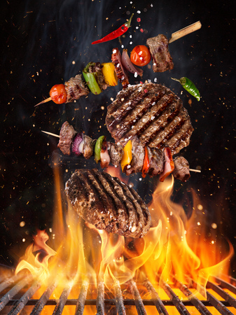 Tasty beef steaks and skewers flying above cast iron grate with fire flames. Stock Photo