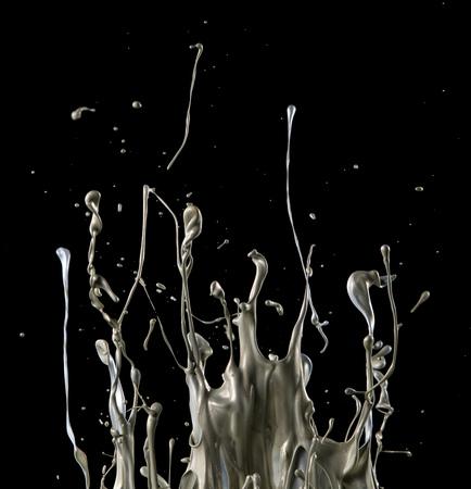 Salpicaduras de líquido plateado abstracto sobre fondo negro Foto de archivo