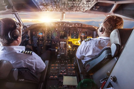 Pilots in the cockpit during a flight with commercial airplane.