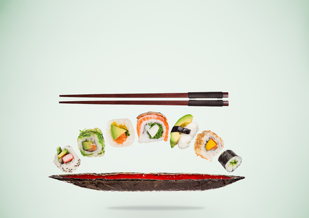 Pieces of delicious japanese sushi frozen in the air. Standard-Bild - 120778631