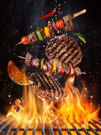 Gustose bistecche di manzo e spiedini che volano sopra la griglia in ghisa con fiamme di fuoco. Archivio Fotografico