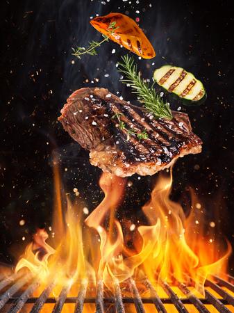 Gustose bistecche di manzo che volano sopra la griglia in ghisa con fiamme di fuoco.