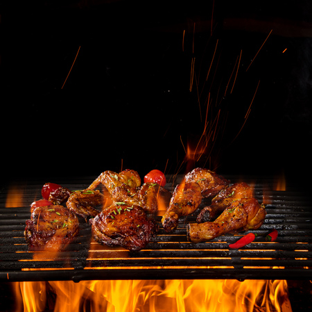 Chicken legs and wings on the grill with flames