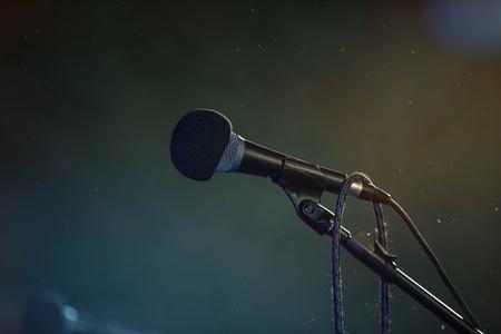 Metal microphone in holder on dark background