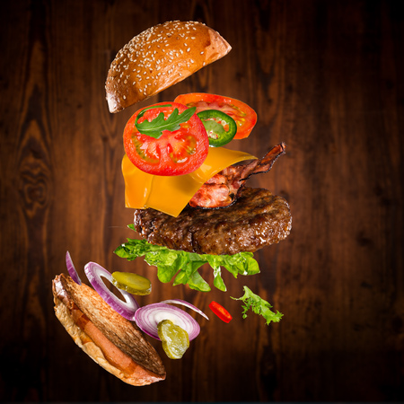 Tasty hamburger with flying ingredients on dark Stok Fotoğraf - 124302854