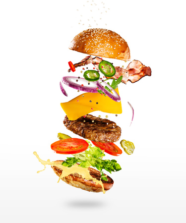 Tasty hamburger with flying ingredients on white