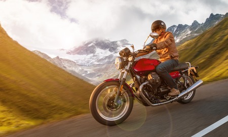 Motorcycle driver riding in Alpine highway, Nockalmstrasse, Austria, Europe. Stok Fotoğraf - 124302920