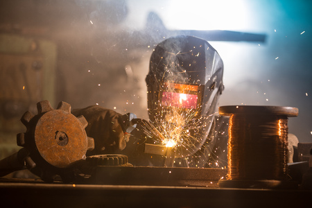 Welder is welding metal part in factory Zdjęcie Seryjne