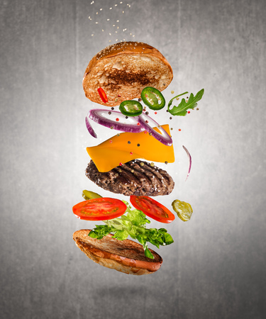 Tasty cheeseburger with flying ingredients on dark