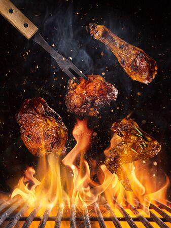 鸡腿和翅膀在烤架上与火焰