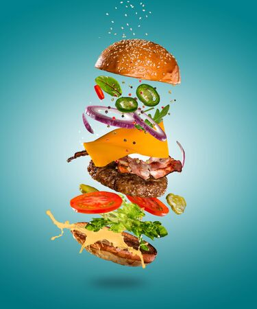 Tasty cheeseburger with flying ingredients on color pastel background