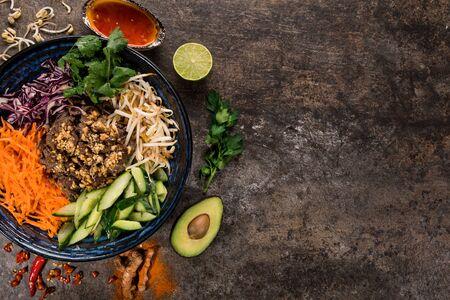 Bun bo nam bo fond de cuisine asiatique avec divers ingrédients sur pierre rustique.