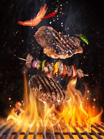 Tasty beef steaks and skewers flying above cast iron grate with fire flames. Banque d'images