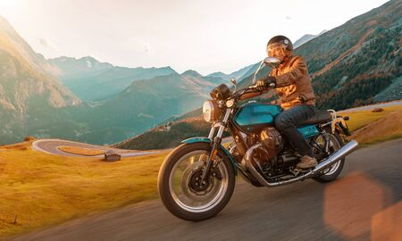 Motorcycle driver riding in Alpine highway, Nockalmstrasse, Austria, Europe. Imagens - 127039472