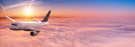 Commercial airplane jetliner flying above dramatic clouds.