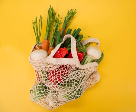 Fresh vegetables in bio eco cotton bags on yellow background. Zero waste shopping concept. Stok Fotoğraf