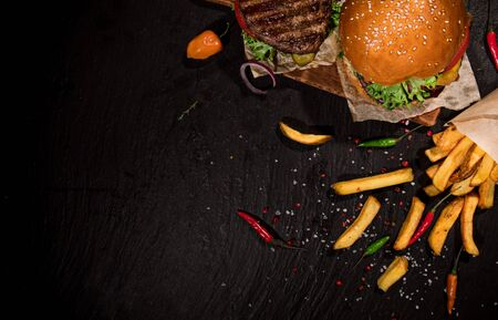 Top view of tasty burgers on black stone table.