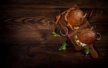 Top view of tasty burgers on wooden table. Zdjęcie Seryjne