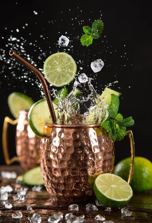 Famous splashing Moscow mule alcoholic cocktail in copper mugs.