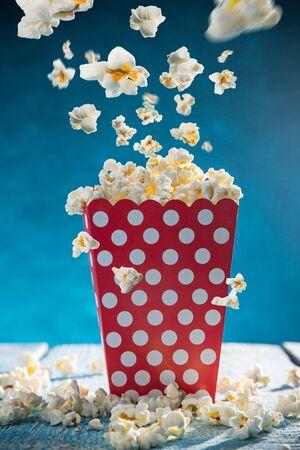 Box of popcorn on blue background. Zdjęcie Seryjne