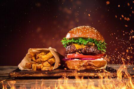 Sabrosa hamburguesa con papas fritas y fuego. Foto de archivo