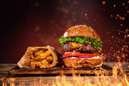 Tasty burger with french fries and fire. Фото со стока