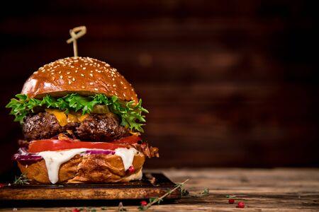 Smaczny burger na drewnianym stole.