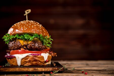 Tasty burger on wooden table.