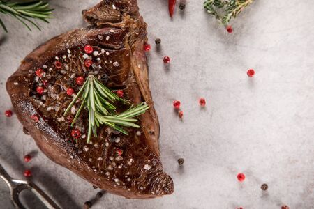 Grilled beef steak on white stone table. Top view.
