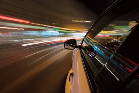 View from side of car moving in a modern night city, blurred motion with lights and cars.
