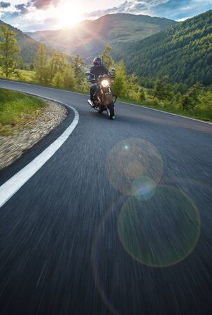 Motorcycle driver riding in Alpine highway, Nockalmstrasse, Austria, central Europe. Reklamní fotografie