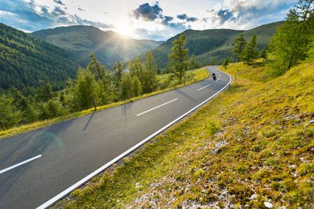 Motorcycle driver riding in Alpine highway, Nockalmstrasse, Austria, central Europe. Stockfoto