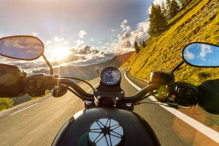 Motorradfahrer, der in alpine Landstraße, Lenkstangenansicht, Österreich, Mitteleuropa reitet.