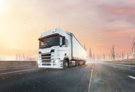 Truck with container on winter road, cargo transportation concept.